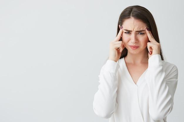 Jovem empresária morena linda segurando os dedos nos templos, franzindo a testa de dor. dor de cabeça.