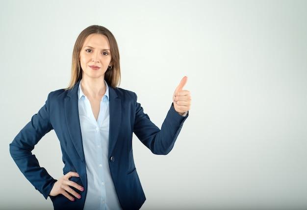 Jovem empresária mostra o polegar isolado no fundo cinza