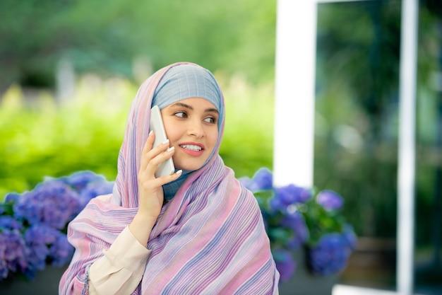 Jovem empresária muçulmana de sucesso em hijab, consultando alguém no smartphone enquanto relaxa ao ar livre