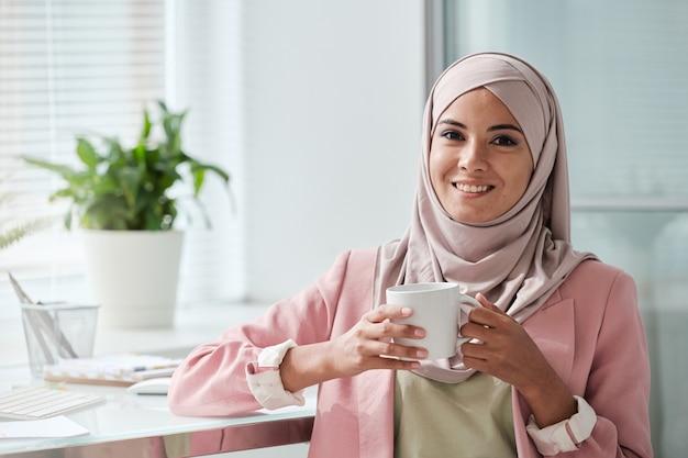Jovem empresária muçulmana de sucesso em hijab e roupa casual elegante, parada no local de trabalho e tomando chá ou café