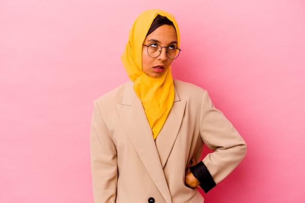 Jovem empresária muçulmana isolada em uma parede rosa cansada de uma tarefa repetitiva