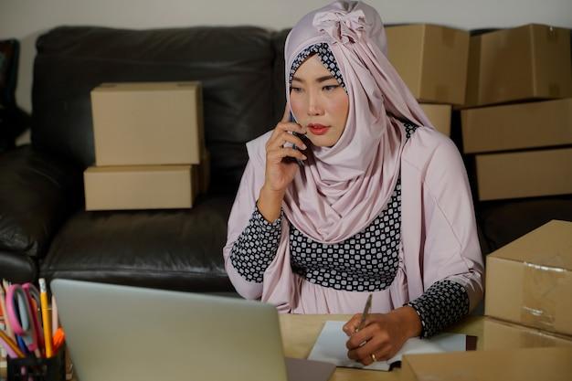 Jovem empresária muçulmana na ásia verifica os pedidos de produtos de estoque e os salva no tablet do escritório em casa. proprietário de pequena empresa envia mercado online durante o surto de covid-19, o conceito