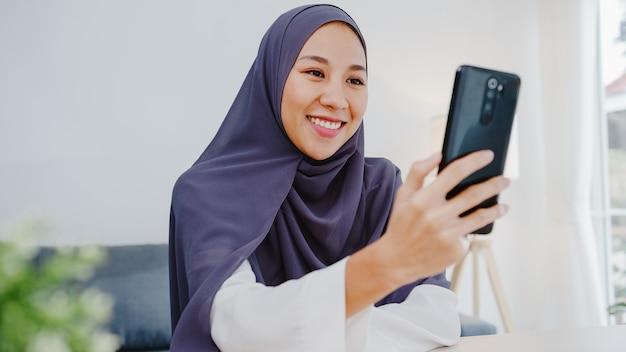Jovem empresária muçulmana usando telefone inteligente, conversa com um amigo por videochat, brainstorm, reunião on-line enquanto trabalha remotamente em casa na sala de estar.