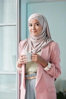 Jovem empresária muito muçulmana em hijab, casaquinho rosa e calça em pé na porta do escritório tomando chá ou café
