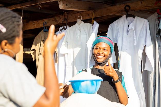 Jovem empresária negra africana usando máscara facial fazendo compras pagando contas em dinheiro.