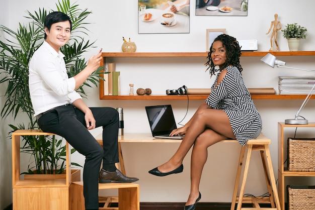 Jovem empresária negra muito sorridente trabalhando em um laptop quando seu colega respondendo a mensagens de texto