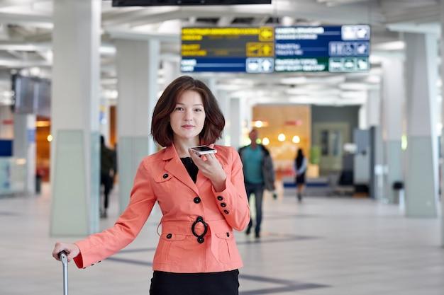 Jovem empresária no aeroporto com bagagem, grava uma mensagem de áudio no telefone e sorrindo.