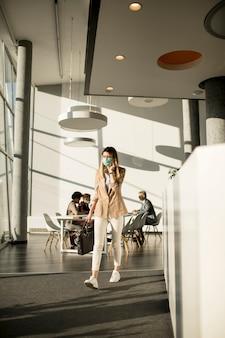 Jovem empresária no celular andando no escritório e usando máscara como proteção contra vírus
