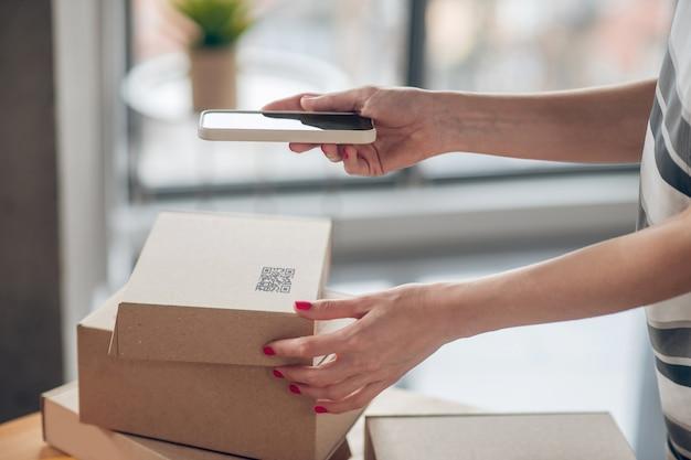 Jovem empresária ocupada preparando mercadorias para envio