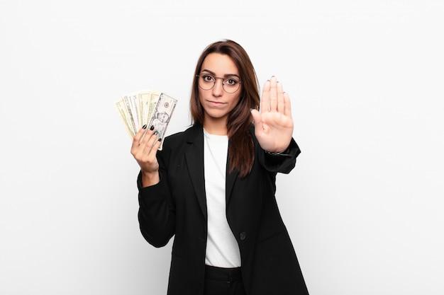 Jovem empresária olhando sério, popa, descontente e com raiva, mostrando a palma da mão aberta, fazendo o gesto de parada com notas de dólar