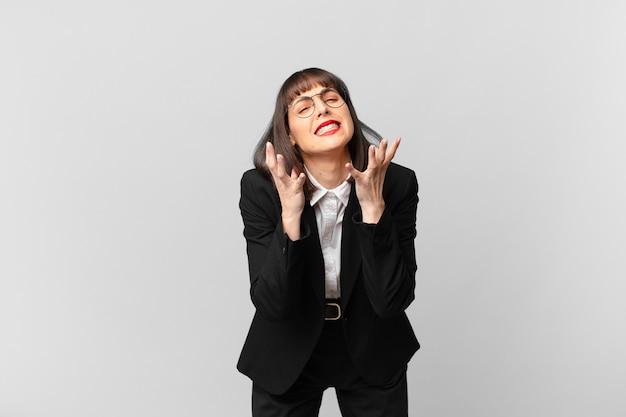 Jovem empresária parecendo desesperada e frustrada, estressada, infeliz e irritada, gritando e gritando