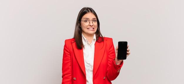 Jovem empresária parecendo perplexa e confusa, mordendo o lábio com um gesto nervoso, sem saber a resposta para o problema
