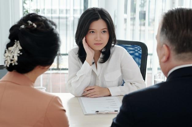 Jovem empresária pensativa discutindo cv do candidato com o gerente de rh e o chefe do departamento na reunião