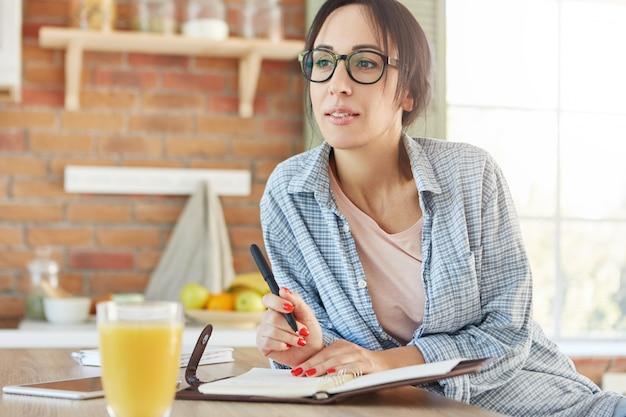 Jovem empresária pensativa planeja seu dia de trabalho, gosta de fins de semana, usa roupas casuais para casa,