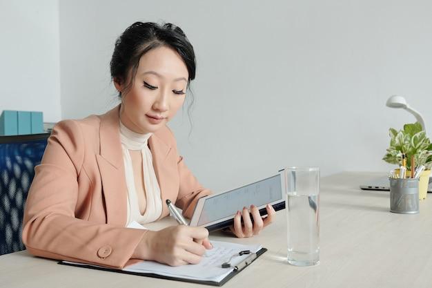 Jovem empresária preenchendo formulário cv e escrevendo carta de apresentação ao procurar emprego