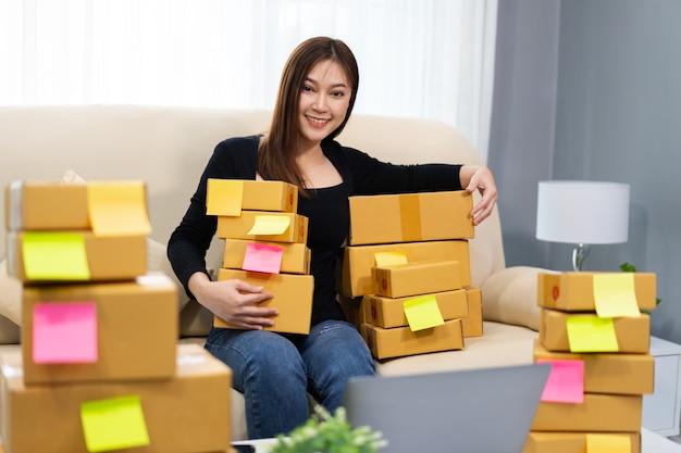 Jovem empresária prepara caixa de encomendas no escritório em casa