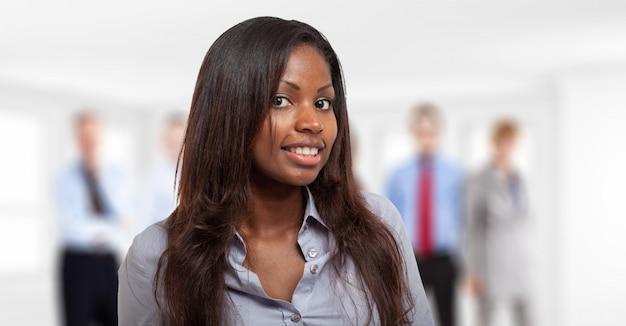 Jovem empresária preta na frente de um grupo de pessoas de negócios