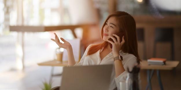 Jovem empresária profissional falando ao telefone com seu cliente no escritório