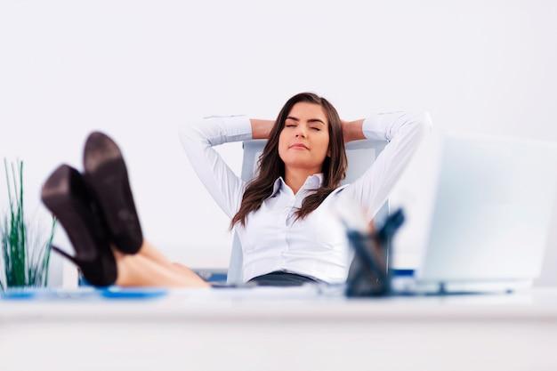Jovem empresária relaxando no escritório