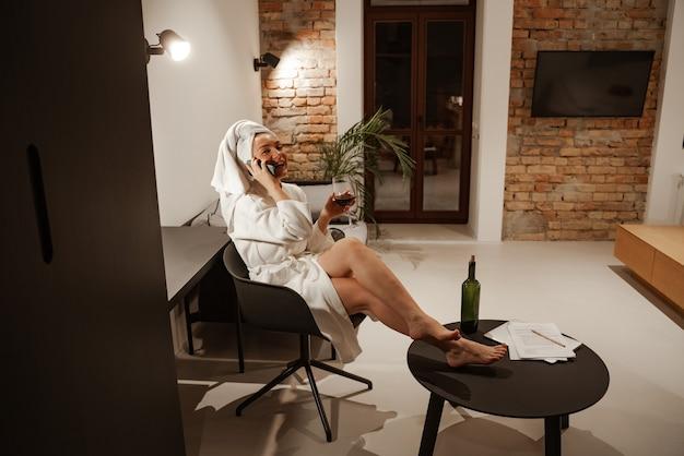 Jovem empresária ruiva tomando uma taça de vinho em casa após um longo dia de trabalho