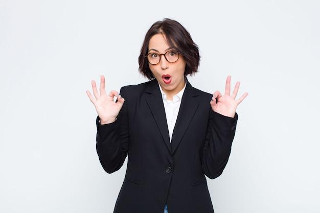 Jovem empresária se sentindo chocado, surpreso e surpreso, mostrando aprovação, fazendo sinal de bem com as duas mãos contra a parede branca