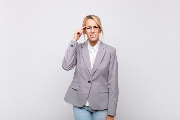 Jovem empresária se sentindo confusa e perplexa, mostrando que você é louco, louco ou maluco