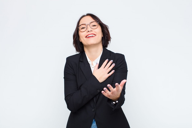 Jovem empresária se sentindo feliz e apaixonada, sorrindo com uma mão ao lado do coração e a outra esticada na frente contra a parede branca