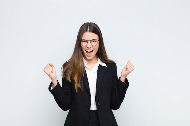 Jovem empresária se sentindo feliz, positiva e bem sucedida, comemorando a vitória, realizações ou boa sorte contra a parede branca