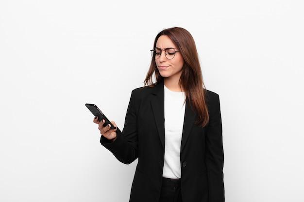 Jovem empresária se sentindo triste, chateada ou com raiva e olhando para o lado com uma atitude negativa, franzindo a testa em desacordo e segurando um telefone móvel