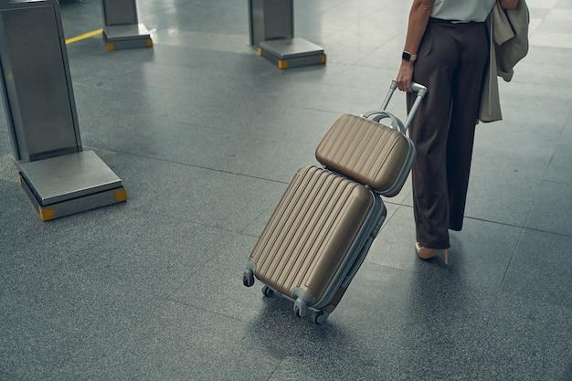 Jovem empresária segurando o casaco com a mão direita enquanto está sozinha no aeroporto