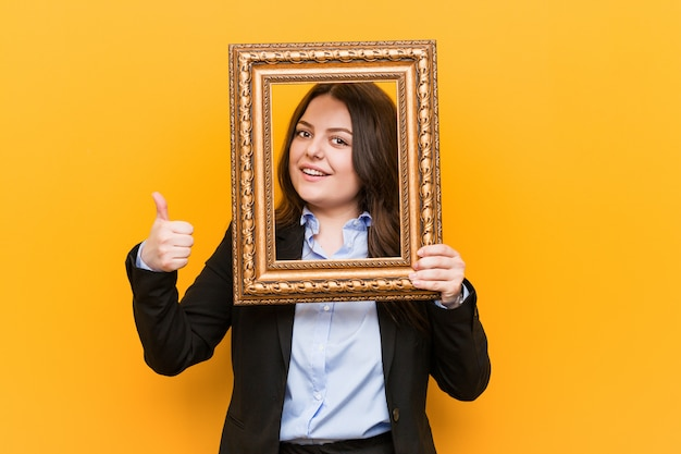 Jovem empresária segurando um quadro sorrindo e levantando o polegar