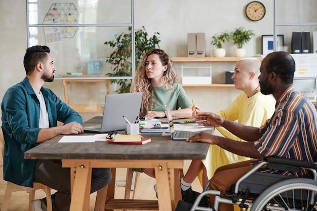 Jovem empresária sentada à mesa junto com seus parceiros, discutindo e trabalhando em equipe durante uma reunião de negócios