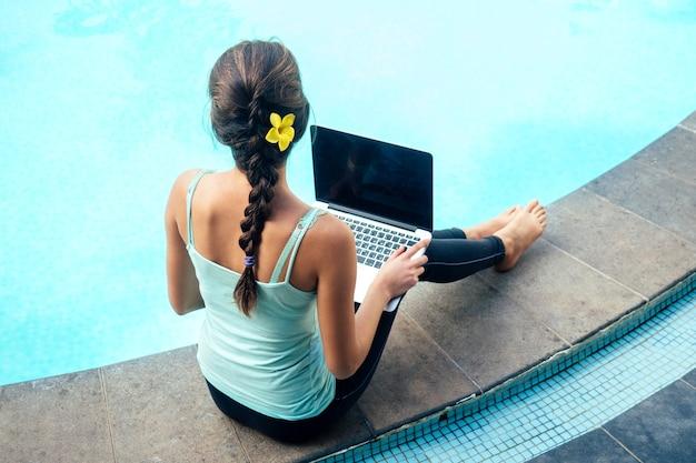 Jovem empresária sentada com laptop de férias perto da piscina