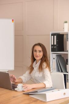 Jovem empresária sentada em seu local de trabalho enquanto faz um relatório de negócios, calcula números anuais, lê documentos e usa tecnologias modernas