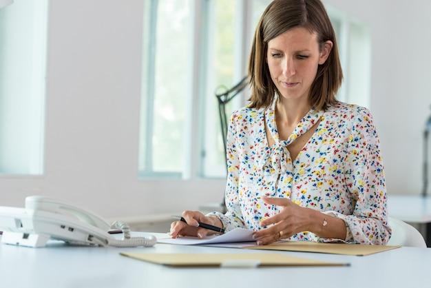 Jovem empresária sentada em sua mesa de escritório trabalhando passando por uma papelada.