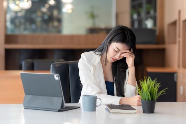 Jovem empresária sentada em uma cadeira em um escritório, cansada de trabalhar no escritório.