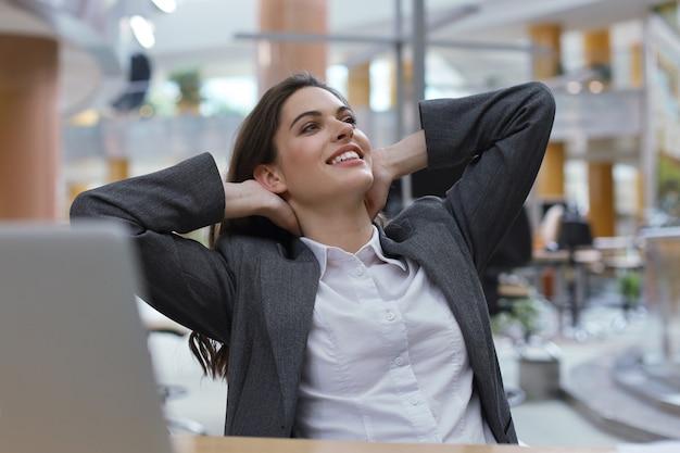 Jovem empresária sentada na mesa do escritório de mãos dadas atrás da cabeça, relaxar se sentir bem.