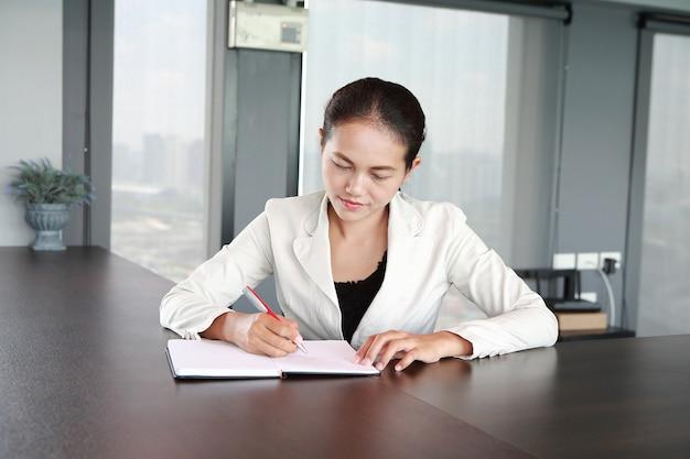 Jovem empresária sentado à mesa no local de trabalho no escritório e por escrito
