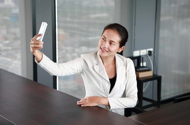 Jovem empresária sentado à mesa no local de trabalho no escritório usando o smartphone tirando fotos de si mesma