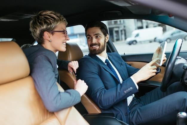 Jovem empresária sentado na limusine e conversando com seu motorista. conceito de negócios.