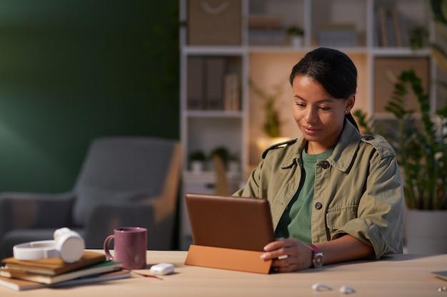 Jovem empresária séria concentrada em seu trabalho online na mesa, ela usando o tablet digital no escritório