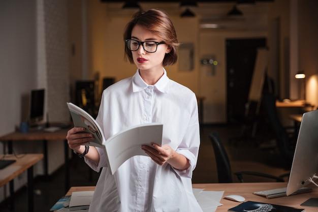 Jovem empresária séria de óculos lendo revista no escritório
