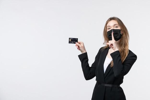 Jovem empresária séria de terno usando sua máscara médica e mostrando o cartão do banco, fazendo gesto de silêncio na parede branca