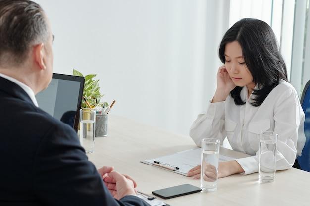 Jovem empresária séria olhando para o cv ao falar com o gerente de rh na mesa do escritório