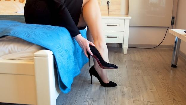 Jovem empresária sexy tirando sapatos de salto alto após um árduo dia de trabalho no escritório