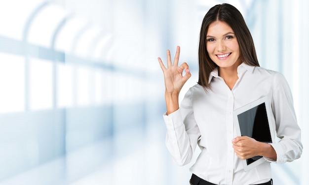 Jovem empresária sorridente com o tablet pc no fundo