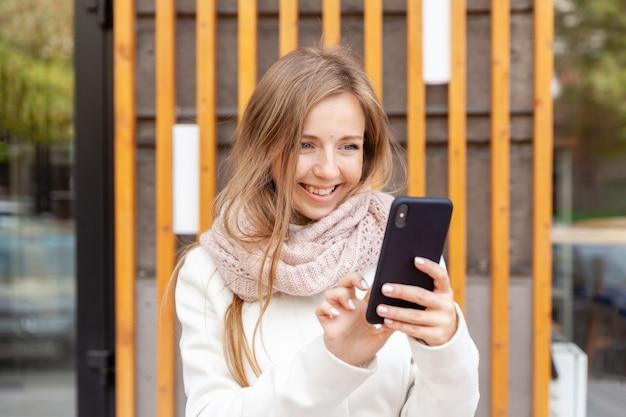 Jovem empresária sorridente no jaleco branco usando smartphone