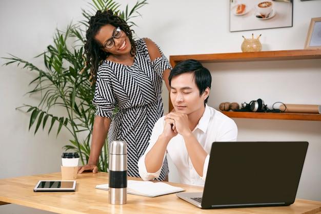Jovem empresária sorridente, olhando para o colega pensando ou meditando com os olhos fechados