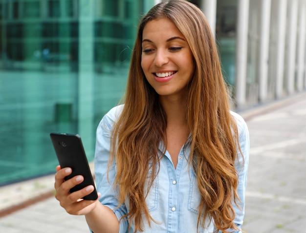 Jovem empresária sorridente usando seu telefone inteligente em frente a um prédio de escritórios