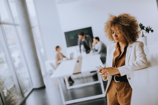 Jovem empresária sorridente usando telefone celular em um escritório moderno